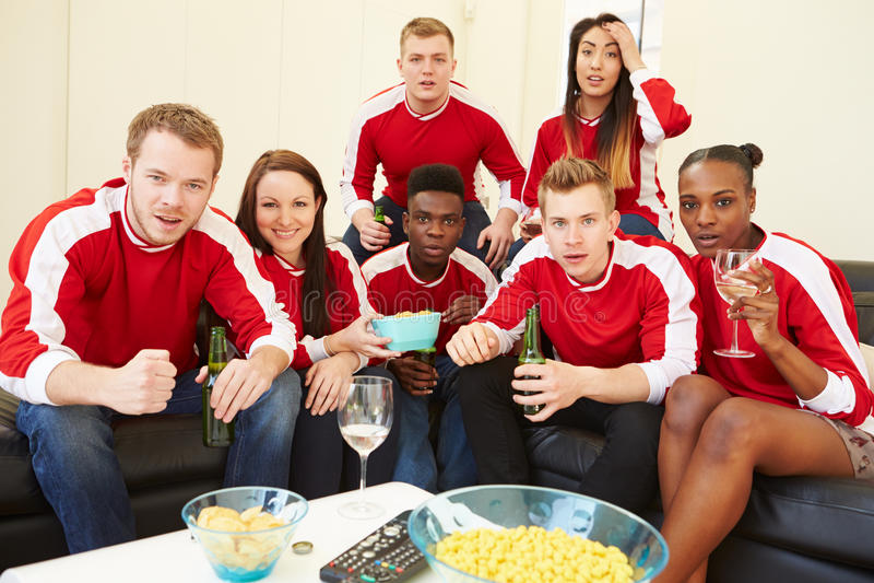 Grupo de fans de deportes que miran el juego en la TV en casa foto de archivo