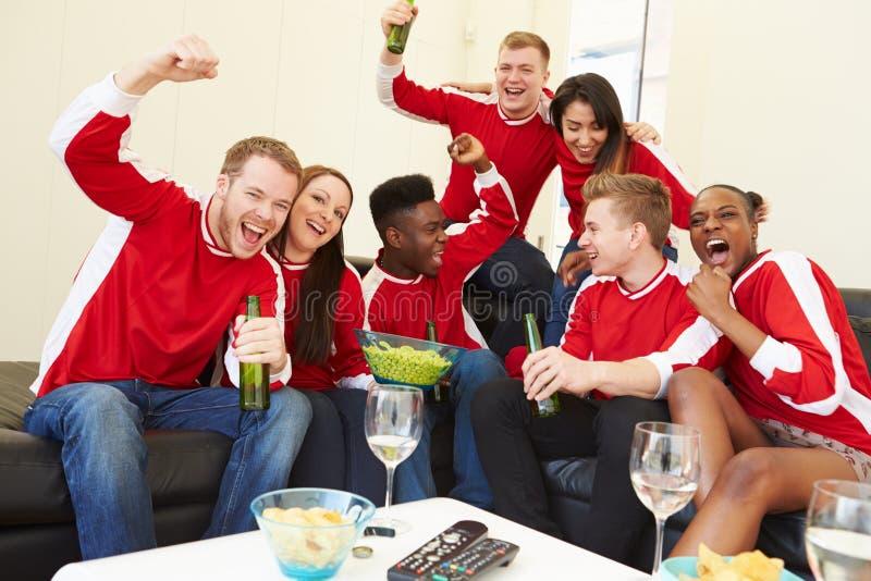 Grupo de fans de deportes que miran el juego en la TV en casa fotografía de archivo libre de regalías
