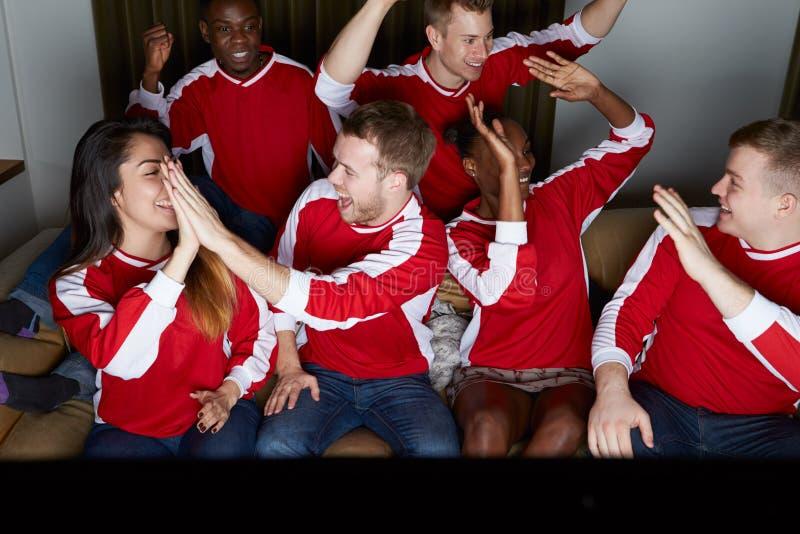 Grupo de fans de deportes que miran el juego en la TV en casa fotos de archivo