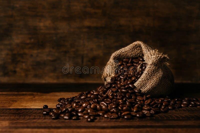 Grupo de feijões de café roasted frescos com saco de serapilheira em uma tabela de madeira foto de stock