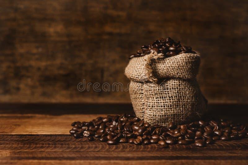 Grupo de feijões de café roasted frescos com saco de serapilheira em uma tabela de madeira fotos de stock royalty free