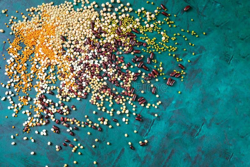 Grupo de feijões dispersados no fundo verde esmeralda com espaço da cópia fotos de stock