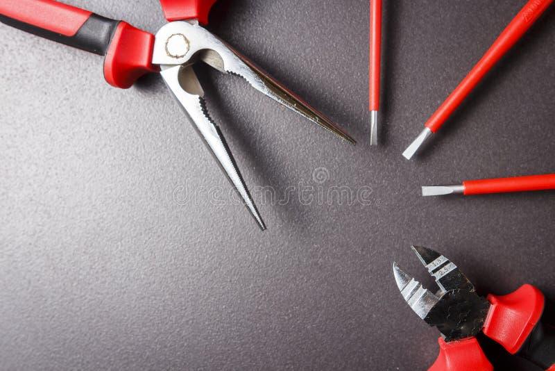 Grupo de ferramentas do eletricista no fundo preto O cortador do ornitorrinco, da chave de fenda e de fio é alinhado com fã imagens de stock royalty free