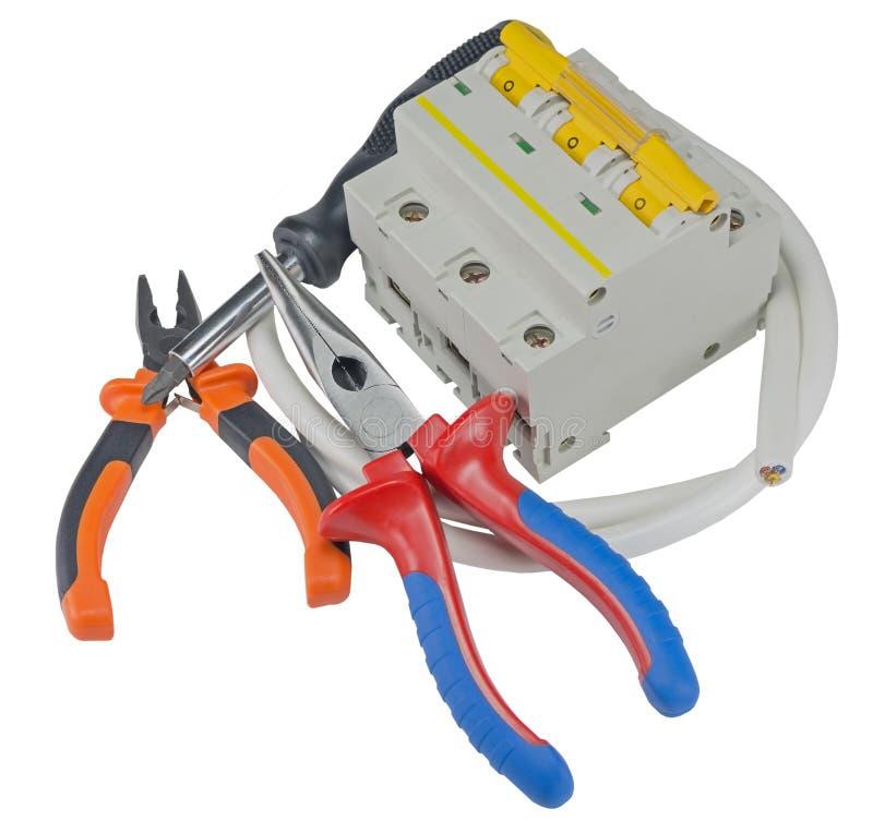 Grupo de ferramentas e de equipamento do eletricista e uma bobina do fio em um w imagens de stock royalty free