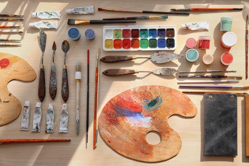 Grupo de ferramentas de pintura na tabela, configuração lisa imagem de stock royalty free