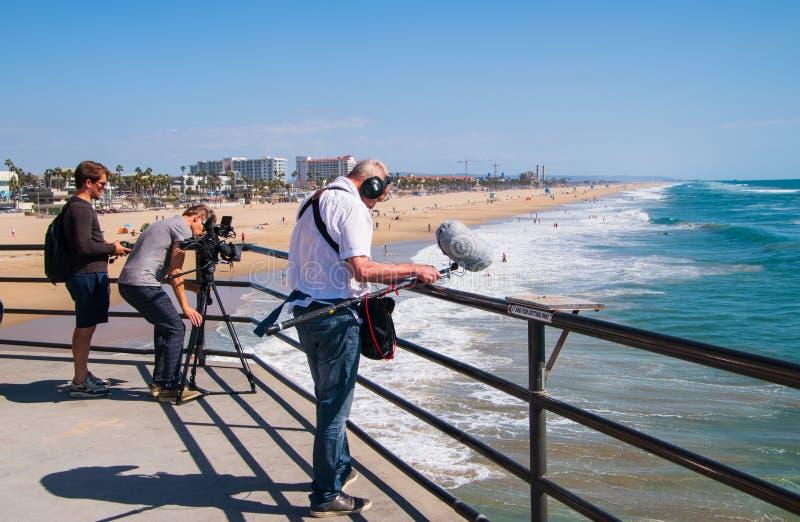 Grupo de filme que filma surfistas no Oceano Pacífico do cais do Huntington Beach imagens de stock royalty free