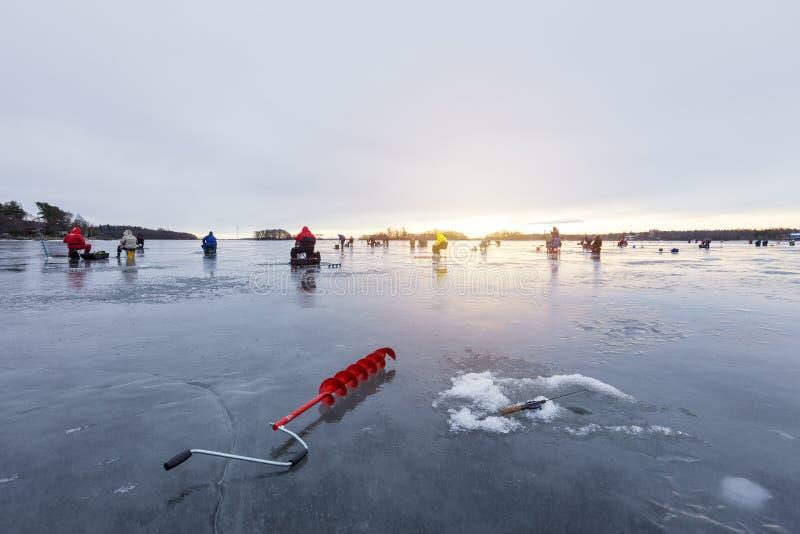 Grupo de fishermens en la pesca del invierno en el hielo en la puesta del sol fotografía de archivo libre de regalías