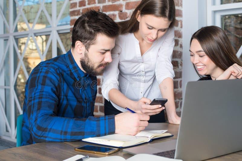 Grupo de freelancers experimentados que miran el vídeo en el teléfono de célula durante día del trabajo imagen de archivo