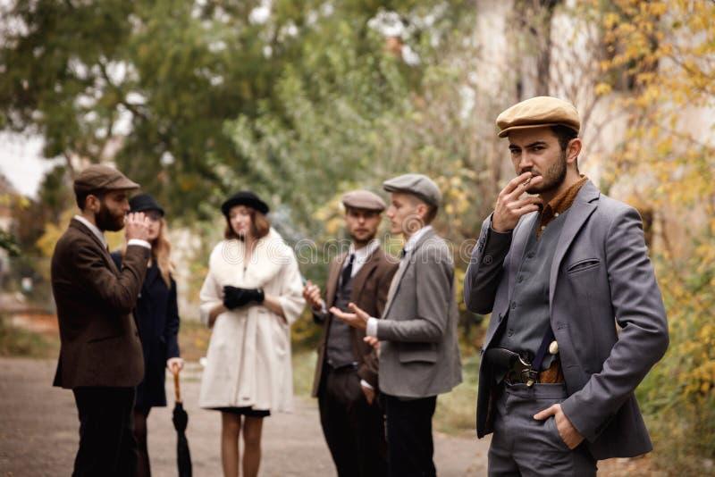 Grupo de gángsteres retros peligrosos en el parque, fumando fotos de archivo libres de regalías