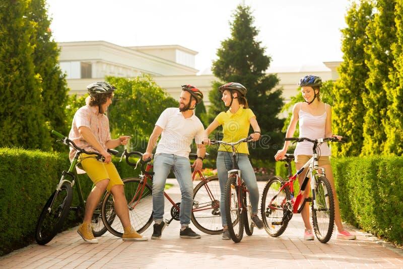 Grupo de gente alegre con las bicicletas afuera foto de archivo
