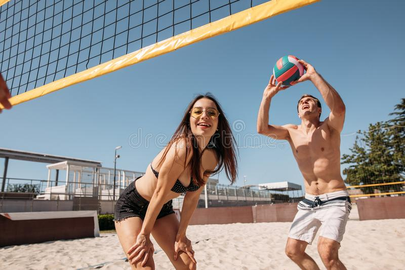 Grupo de gente alegre joven que juega a voleibol de playa el día soleado foto de archivo libre de regalías