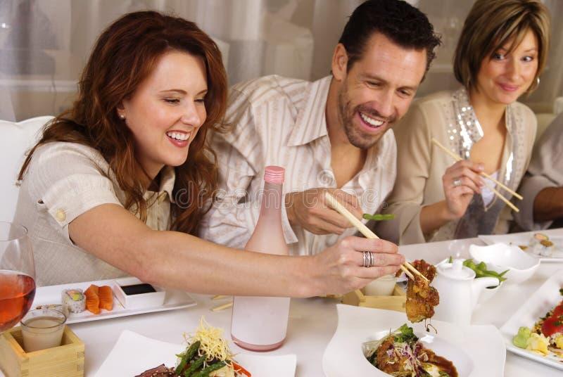 Grupo de gente atractiva que come y que socializa