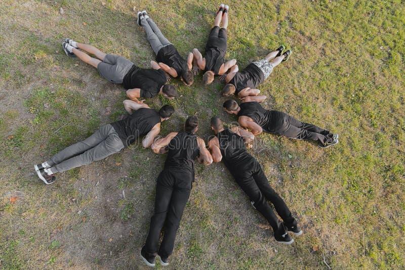 Grupo de gente de la aptitud que hace pectorales en parque foto de archivo libre de regalías