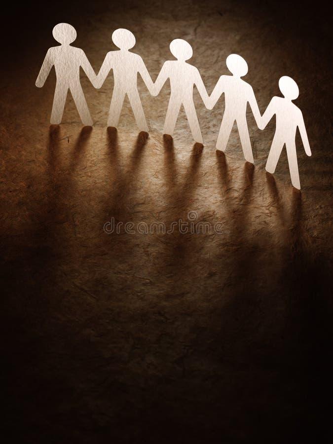 Grupo de gente de papel que lleva a cabo las manos. fotografía de archivo