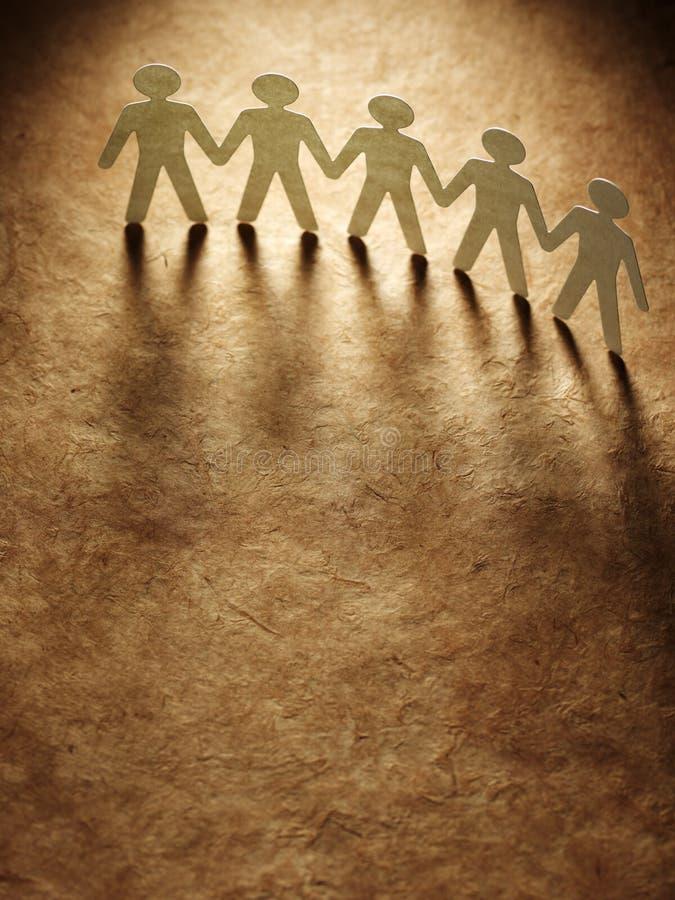 Grupo de gente de papel que lleva a cabo las manos. foto de archivo