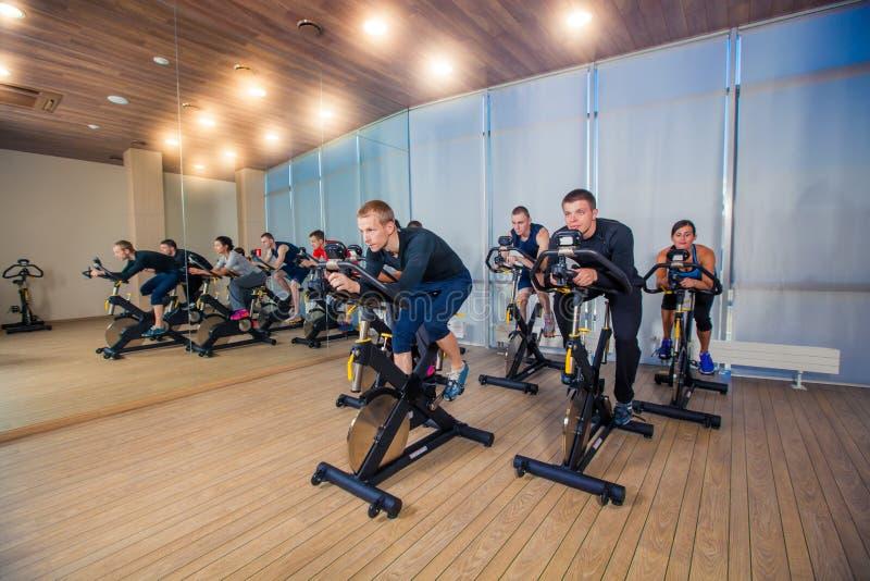 Grupo de gente del gimnasio en las máquinas, completando un ciclo en clase imagen de archivo libre de regalías