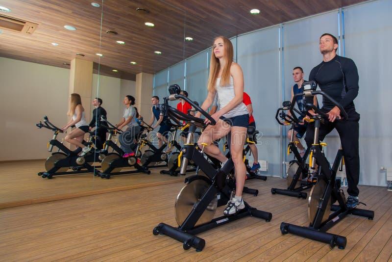 Grupo de gente del gimnasio en las máquinas, completando un ciclo en clase foto de archivo