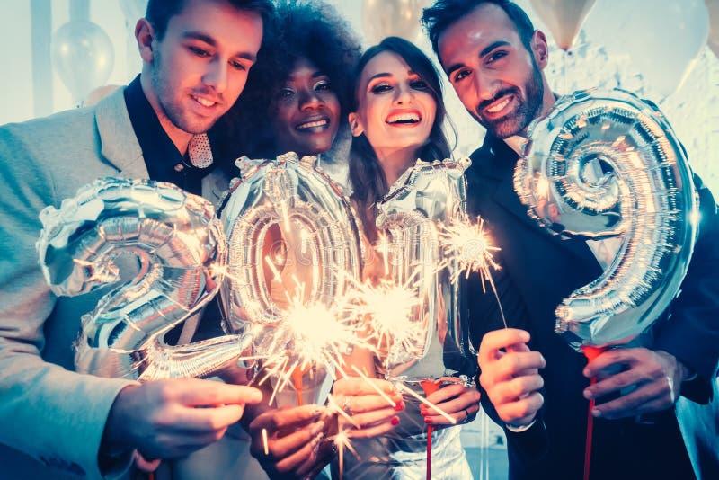 Grupo de gente del partido que celebra la llegada de 2019 foto de archivo