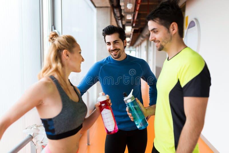 Grupo de gente deportiva que se relaja y que habla después de clase en gimnasio imagen de archivo