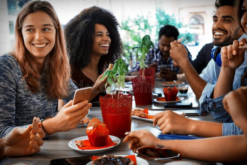 Grupo de gente diversa joven que se sienta en la tabla del restaurante que tiene una comida junto fotos de archivo libres de regalías