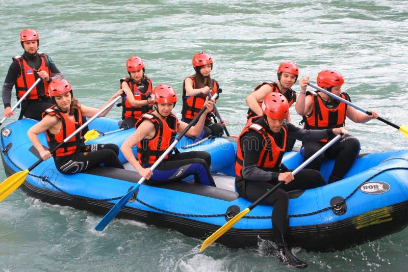 Grupo de gente feliz con transportar de whitewater de la guía y remar o en balsa fotografía de archivo