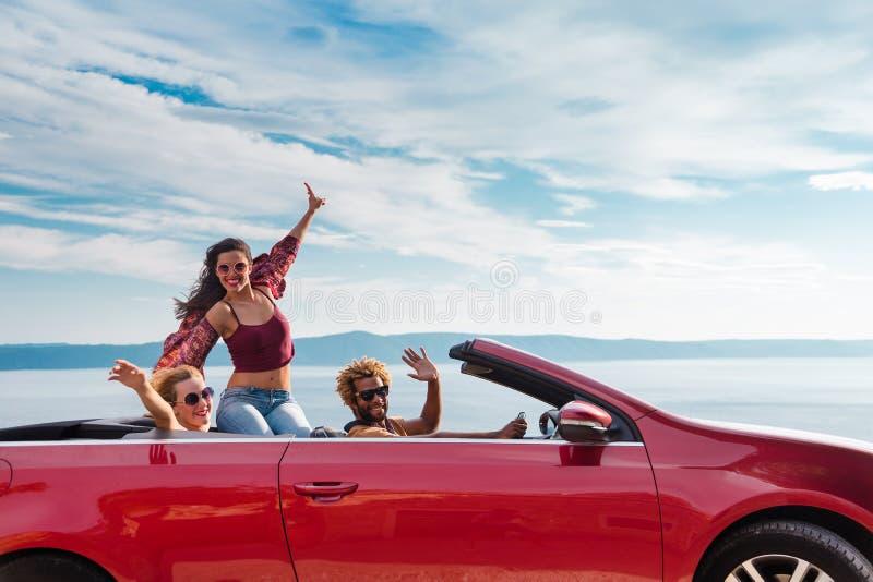 Grupo de gente feliz en coche convertible rojo foto de archivo libre de regalías