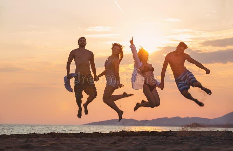 Grupo de gente feliz que baila y que salta dentro del mar fotos de archivo