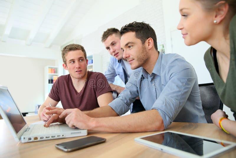 Grupo de gente joven en el entrenamiento del negocio con el ordenador portátil imagen de archivo