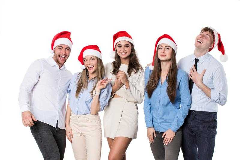 Grupo de gente joven feliz en los sombreros de santa en el fondo blanco imagenes de archivo