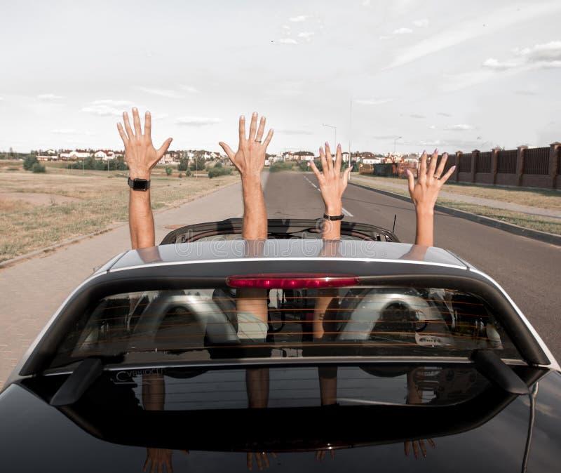 Grupo de gente joven feliz que agita de un coche convertible fotografía de archivo libre de regalías