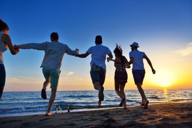 Grupo de gente joven feliz que baila en la playa en puesta del sol hermosa del verano imágenes de archivo libres de regalías