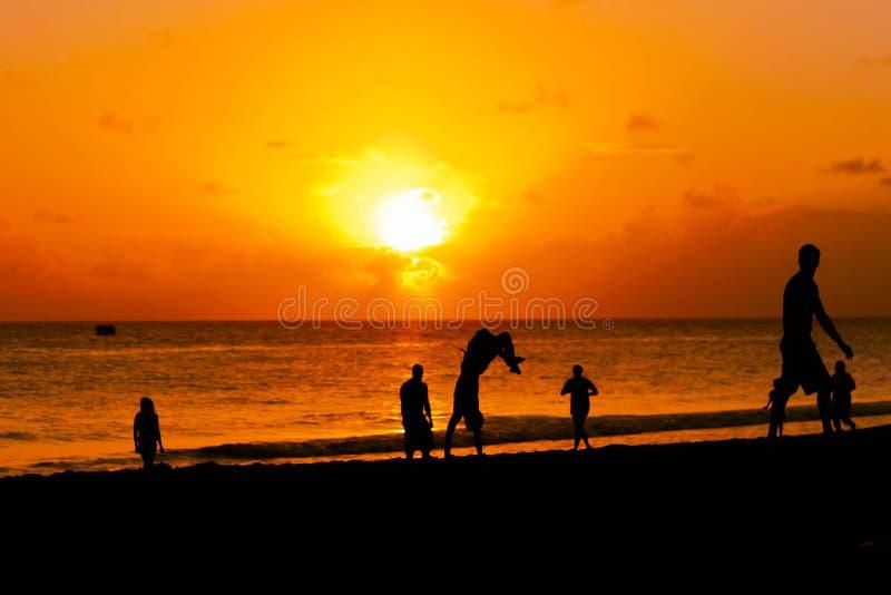 Grupo de gente joven feliz que salta por la puesta del sol de la playa fotos de archivo libres de regalías