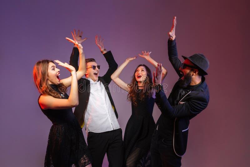 Grupo de gente joven feliz que se coloca así como las manos aumentadas fotografía de archivo