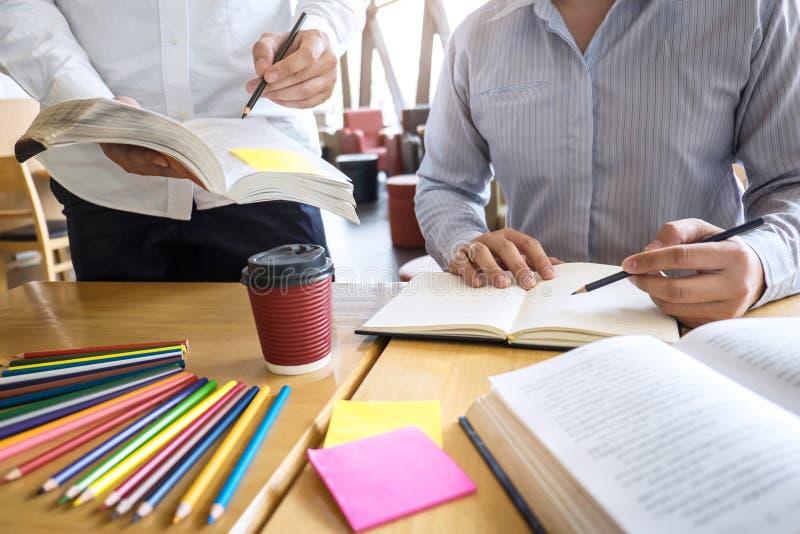 Grupo de gente joven que aprende estudiando la nueva lecci?n al conocimiento en biblioteca durante la ayuda ense?ando a la educac foto de archivo libre de regalías