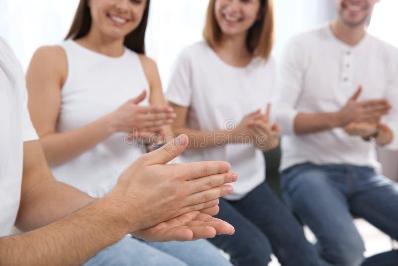 Grupo de gente joven que aprende lenguaje de signos con el profesor dentro fotos de archivo
