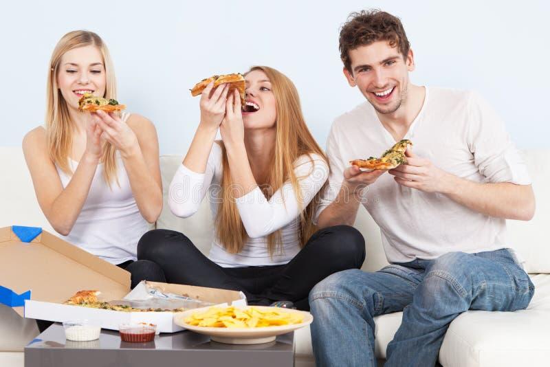 Grupo de gente joven que come la pizza en casa imágenes de archivo libres de regalías
