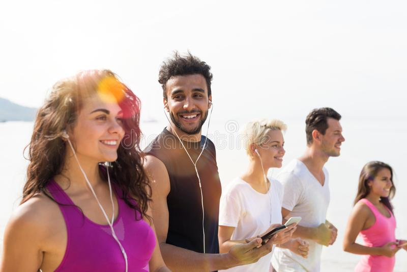Grupo de gente joven que corre en la sonrisa feliz de la playa, de corredores del deporte de la raza de la mezcla que activan res imagenes de archivo