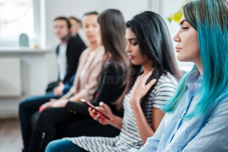 Grupo de gente joven que espera una entrevista del bastidor o de trabajo imagen de archivo libre de regalías