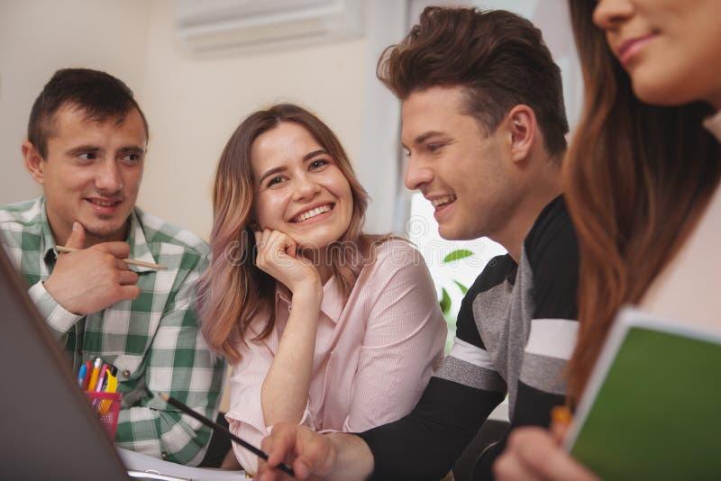 Grupo de gente joven que estudia junto en la sala de clase de la universidad fotografía de archivo