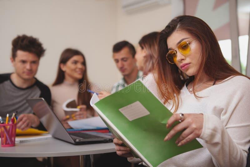 Grupo de gente joven que estudia junto en la sala de clase de la universidad fotos de archivo