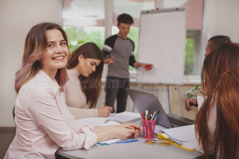 Grupo de gente joven que estudia junto en la sala de clase de la universidad imagen de archivo