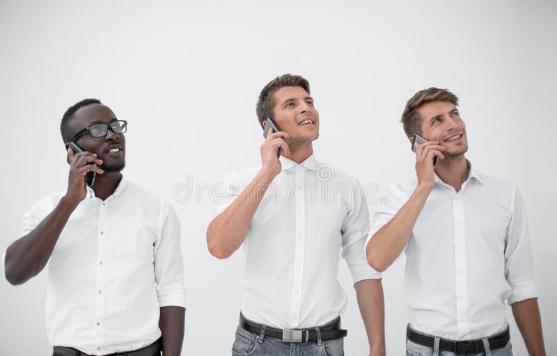 Grupo de gente joven que habla en móvil y que mira el spac de la copia fotos de archivo libres de regalías
