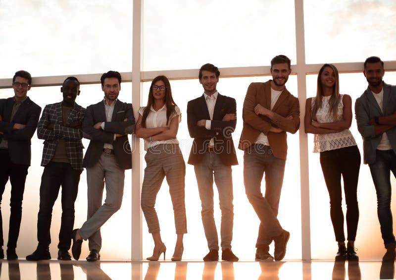Grupo de gente joven que se coloca en una oficina con una ventana grande imagen de archivo
