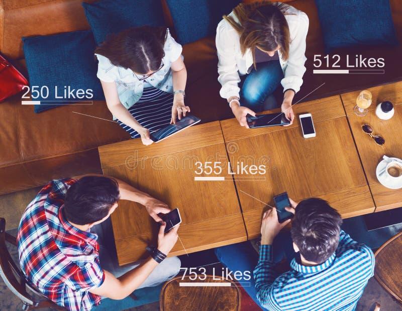 Grupo de gente joven que se sienta en un café, contando gustos imágenes de archivo libres de regalías