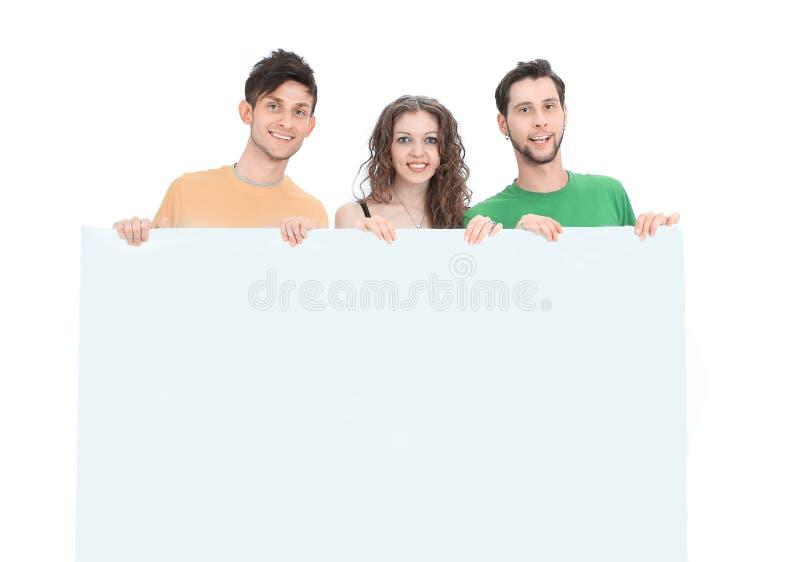 Grupo de gente joven que sostiene un cartel en blanco grande fotografía de archivo