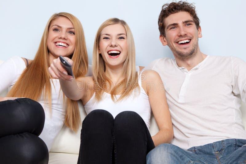Grupo de gente joven que ve la TV en casa fotos de archivo