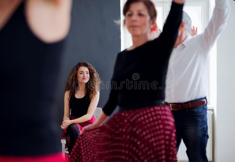 Grupo de gente mayor en clase de baile con el profesor de la danza, midsection imagen de archivo