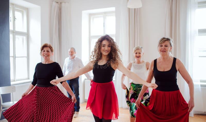 Grupo de gente mayor en clase de baile con el profesor de la danza foto de archivo