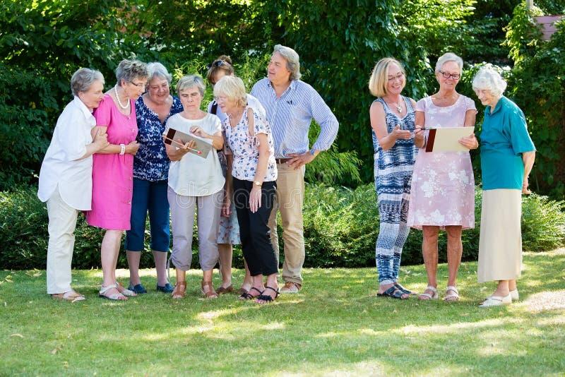 Grupo de gente mayor que discute sus pinturas así como instructor del curso, mientras que se coloca en jardín el día soleado fotografía de archivo