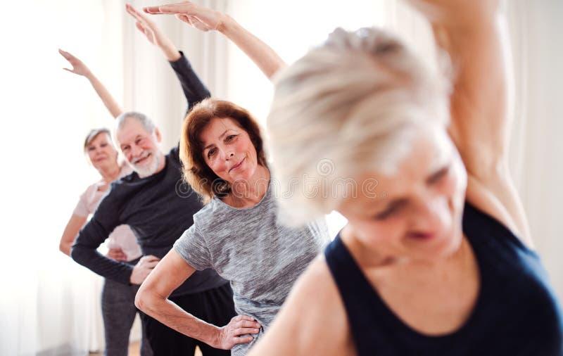 Grupo de gente mayor que hace ejercicio en club del centro de la comunidad foto de archivo